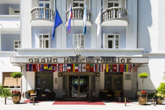 Vhod v Grand Hotel Toplice na Bledu in pročelje hotela z druge strani ceste.